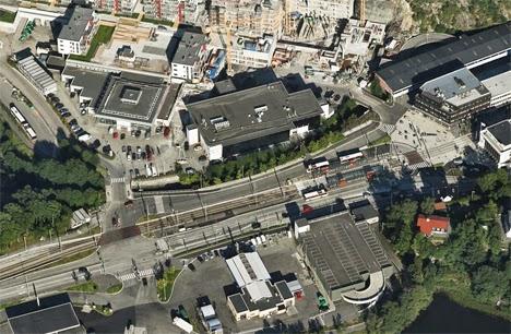 Valkokattoisia busseja raitiotien vaihtopysäkillä. Lähellä rakenteilla uusia kerrostaloja. Kuva: Bing / kuvateksti: Antero Alku